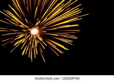 blurred bright, yellow bursts of fireworks on the night sky