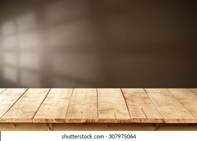 blurred brown wall with shadow space of window and yellow wooden desk top