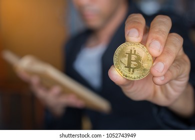 Blurred business man lerning book method of money with holding gold bitcoin coin