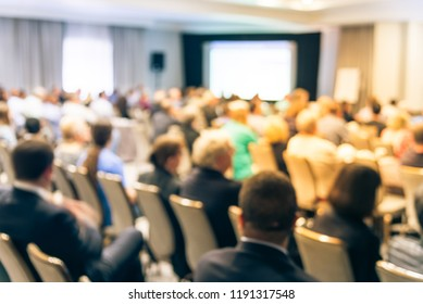 Blurred business seminar meeting with LED projector screen and speaker speech on stage. Defocused rear view audience in conference hall room, listening talk show in USA. Education, business concept