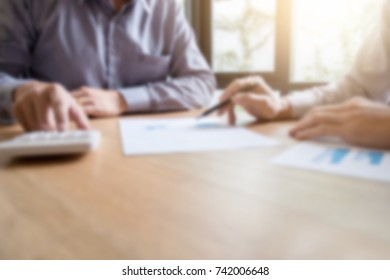Blurred of Business team two executive discussing and analysis working Financial investment on calculator with calculate on tablet Analyze business and market growth on financial document data graph.