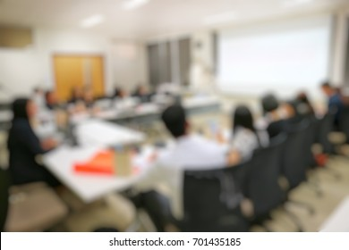 Blurred of a business woman in black suit present with smartboard in meeting room.