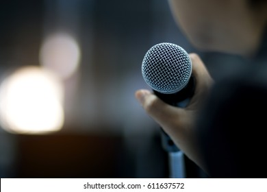 blurred of businessman hand holding microphone for speech presentation in conference hall, Seminar and Speaker Concept. vintage tone