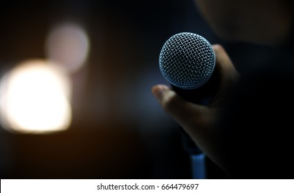 blurred of businessman hand holding microphone for speech presentation in conference hall, vintage tone