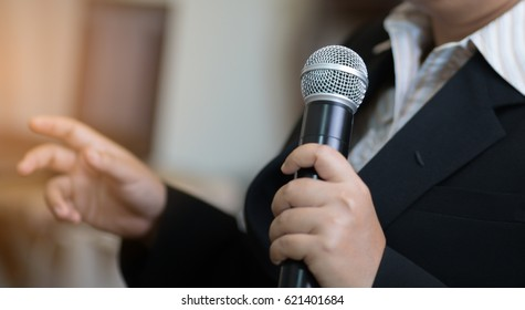 blurred of Businesswoman speech with microphone, hand gesturing protesting or belief concept for explaining in seminar meeting room