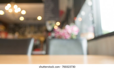 Blurred cafe with empty wooden desk background for montage product display