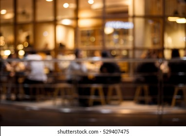 Blurred of cafe ( restaurant ) with light gold in night.For modern lifestyle background.