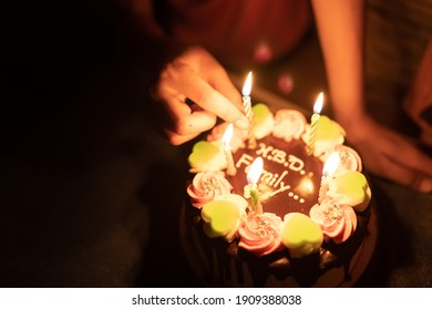 Blurred cake for happy brithday on night background, hand holding candles and fire flame burning it on cake, family happy party, bright light flame on night