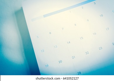 Blurred calendar with pencil in blue tone
