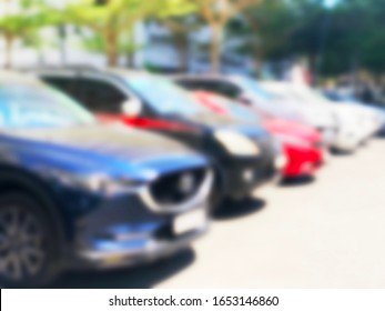 Blurred car background in a parking lot.