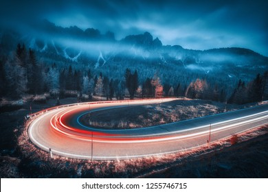 Blurred car headlights on winding road in mountains with low clouds at night in autumn. Moody landscape with asphalt road, light trails, foggy forest, rocks and blue sky at dusk. Roadway in Italy