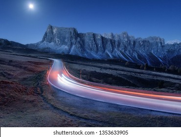 Blurred car headlights on winding road at night in autumn. Landscape with asphalt road, light trails, mountains, hills, blue sky with moonlight at dusk. Roadway in Italy. Moon over highway and rocks