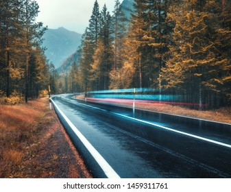 Blurred car on the road in autumn forest in rain. Perfect asphalt mountain road in overcast rainy day. Roadway, orange trees in alps in fall. Nature. Highway in foggy woodland. Car in motion. Travel