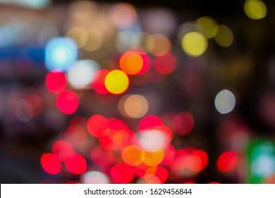 Blurred of car on road in the city at Night time. Defocused of traffic jams have car, bu and motorcycle. Red, Orange, Yellow, White and Blue bokeh light. Blur of light glitter. Glow texture background