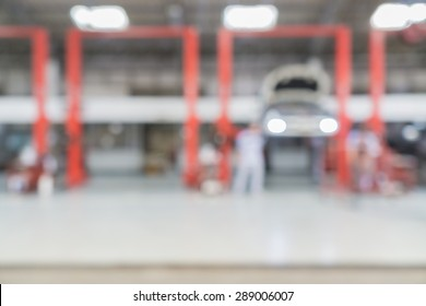Blurred of car technician repairing the car in garage background.