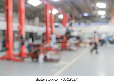 Blurred of car technician repairing the car in garage background, Interior of a car repair station.