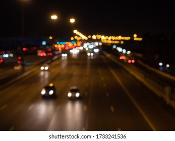 Blurred cars driving on a motorway at night. Seeing bokeh car headlights and taillights on the multiple lanes.