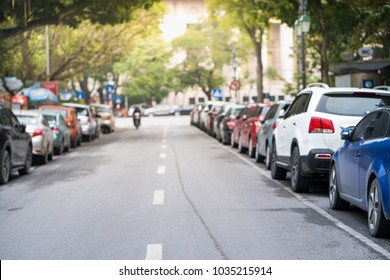 Blurred cars parked on the urban street side