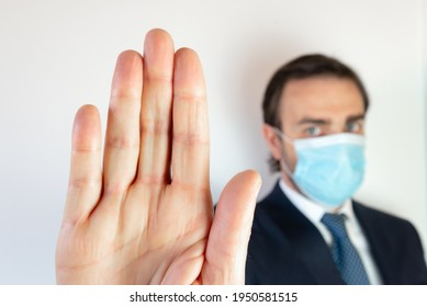 Blurred caucasian man with suit and tie and face mask on white background showing the palm of hand as a signal of alt