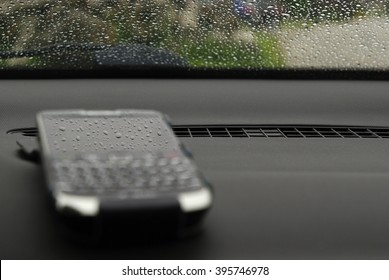 Blurred cell phone with sharp rain drops reflection in its screen. Car dashboard and windscreen with raindrops. Blackberry reflecting raindrops.