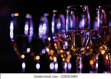 blurred champagne glasses standing in several rows in a dark room with a blue light