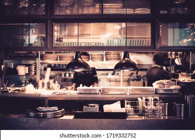 Blurred chef in the open kitchen, working at cooking station in the restaurant and cafe.