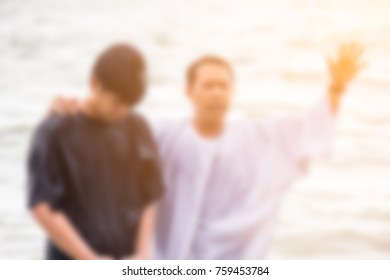 Blurred of a Chirstian pastor baptize a young man at the sea. Pastor is praying for a man.