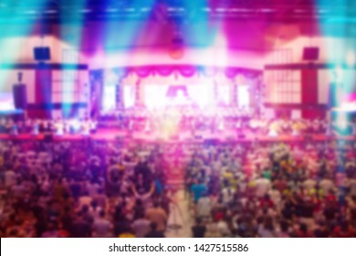 Blurred of Christian Congregation Worship God together in Big Church hall in front of music stage and light effected.