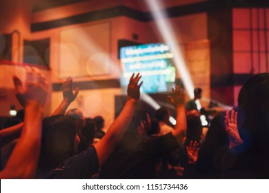 blurred of christian congregation worshiping God in big church hall in front of music stage