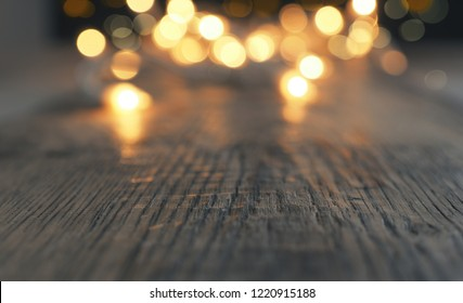 Blurred Christmas lights on a rustic wooden table with space for text or image, selective focus on foreground