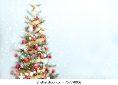 Blurred of Christmas tree and light bokeh with snowfall on winter background