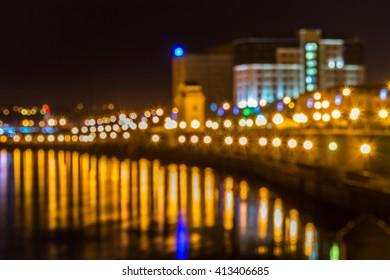 blurred city lights at night. Irkutsk at night. embankment, river, water, reflection.
