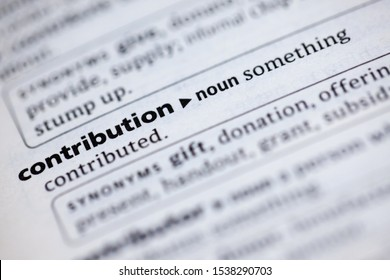Blurred close up to the partial dictionary definition of Contribution
