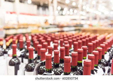 Blurred and close up view group of red wine bottles in cellar at wine section of modern distribution warehouse. Inventory, logistic, business, wholesale, export concept. Beverage alcohol background.