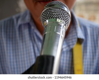blurred of closeup microphone of man singing to a microphone.