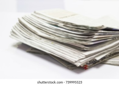 Blurred - Closeup  Newspaper Stack on white table