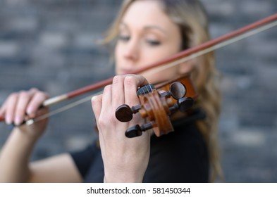 Blurred close-up side portrait of young blonde woman playing violin with focus on the scroll of wooden instrument and left hand of player