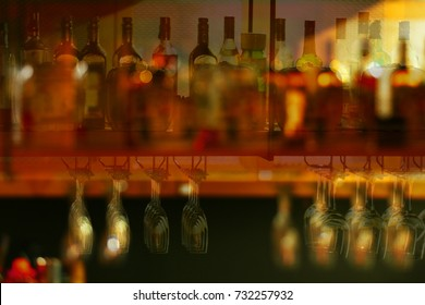 Blurred of Colorful liquor glass bottles at bar, selective focus and free space for text.