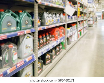 Blurred colorful motor oil bottles on shelves in supermarket as background. Copy space