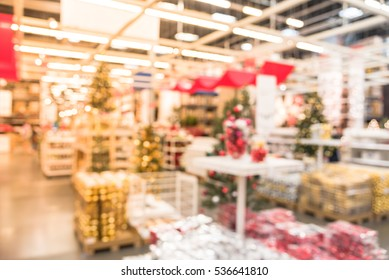 blurred colorful row shelves of plastic christmas bell ornaments garlands lightings and artificial