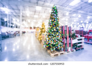 Blurred colorful tall artificial tree decoration and Christmas supplies at wholesale store in Texas, USA. Wreaths and strings of bokeh lights surrounding the Xmas tree. Holiday abstract background