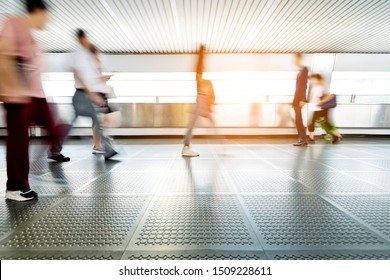 Blurred commuters walking on footbridge.