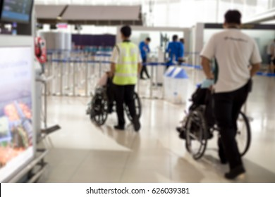 Blurred concept caretaker pushing elderly people in wheelchair at the airport