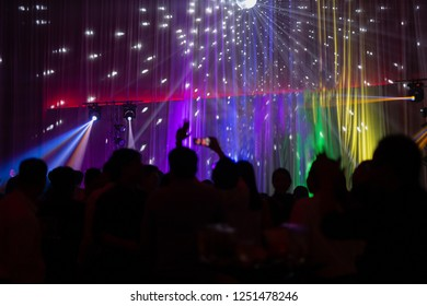Blurred concept at concert party with audience and colourful led lighting