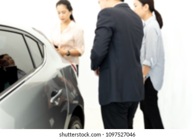 Blurred concept two woman buying a new car with saleman at showroom
