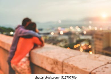 Blurred couple in love sharing emotions with beautiful sunset and panoramic romantic view - Lovers in vacation - Tender moment and romance concept - Blurry bokeh background - Warm vintage filter