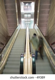 blurred couple on moving escalator