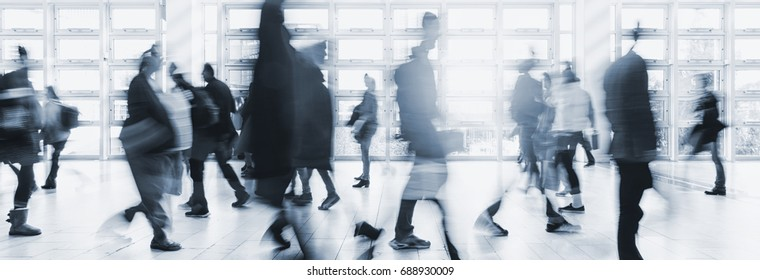 blurred crowd commuting traveling walking in a modern hall