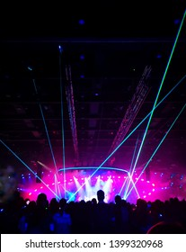 Blurred crowd at concert : Silhouette people crowd happy and cheering in front of colorful stage with bright laser light beam. Music superstar performance. Soft focus