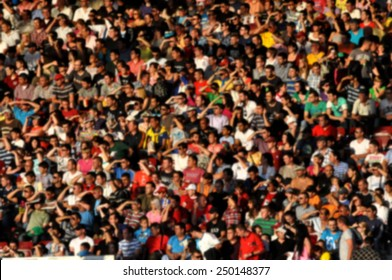 Blurred crowd of people at a football match in a stadium